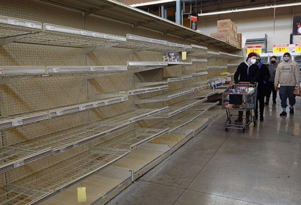 PHOTO: Shoppers walk past a bare shelf at a grocery store, Feb.18, 2021, in Austin, Texas. (Joe Raedle/Getty Images)
