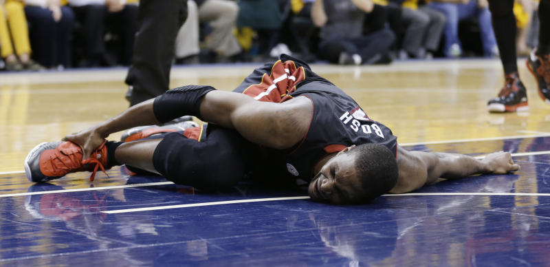 Miami Heat's Chris Bosh holds his ankle during the second half against the Indiana Pacers in Game 4 of the NBA basketball Eastern Conference finals, Tuesday, May 28, 2013, in Indianapolis. (AP Photo/Michael Conroy)