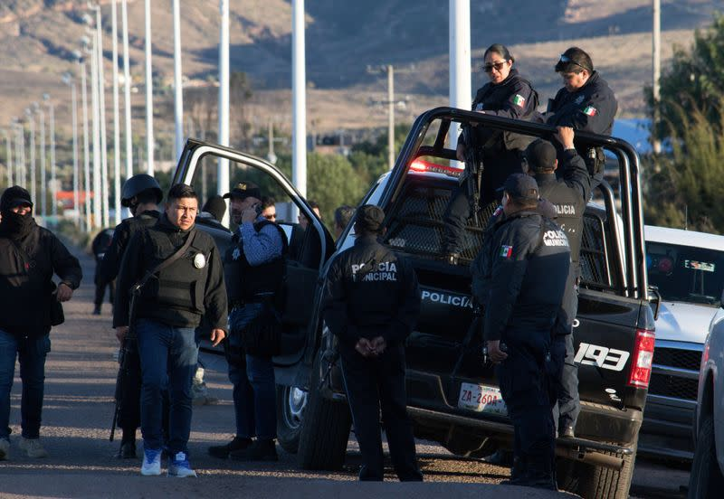 Police officers stand atop a vehicle as they keep watch outside the prison after sixteen inmates were killed and five were wounded in a prison fight at the Regional Center for Social Reintegration in the town of Cieneguillas