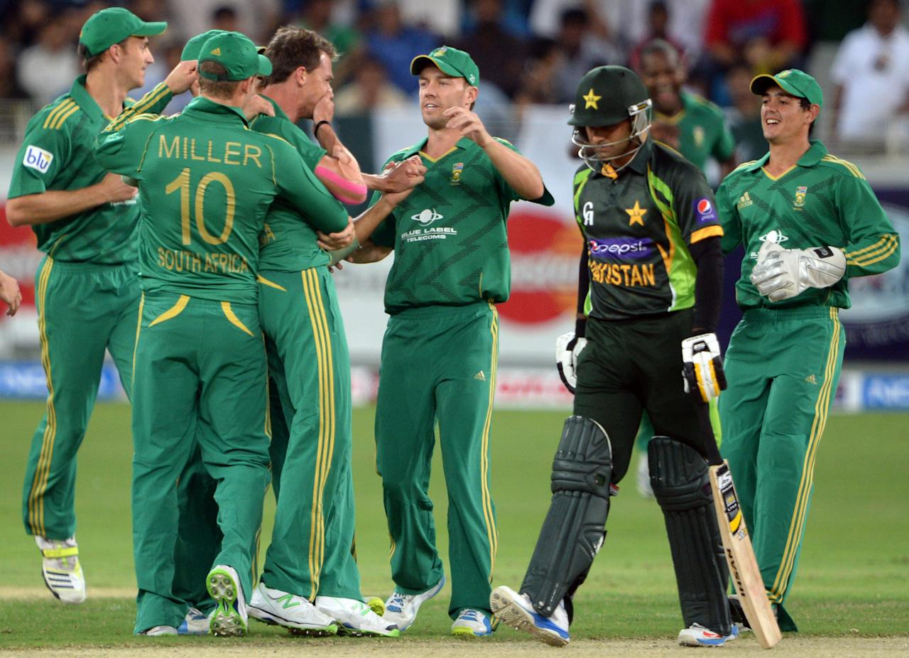 South African bowler Dale Steyn (C) celebrates with teammates after taking a wicket from Pakistani captain Mohammad Hafeez (2nd R) during the First T20 International at Dubai stadium on November 13, 2013. Pakistan won the toss and elected to bat. AFP PHOTO/ ASIF HASSAN        (Photo credit should read ASIF HASSAN/AFP/Getty Images)