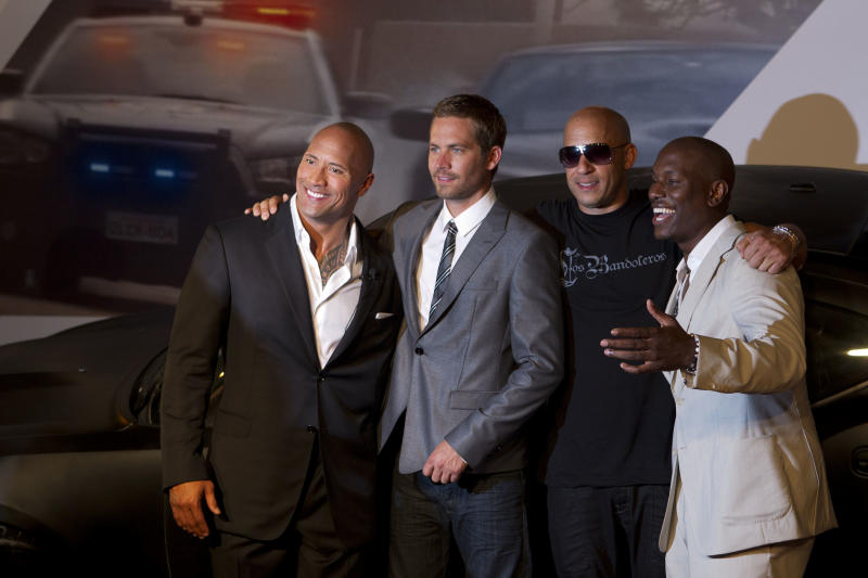 Actors, from left, Dwayne Johnson, Paul Walker, Vin Diesel and Tyrese Gibson pose for photos as they arrive to attend the premiere of the film Fast Five in Rio de Janeiro, Brazil, Friday April 15, 2011. (AP Photo/Felipe Dana)