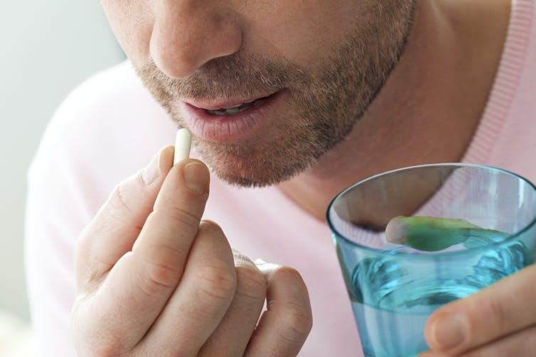 Man taking medication with glass of water.