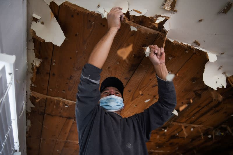 FILE PHOTO: A contractor removes material from a ceiling in a recently-purchased home in Houston