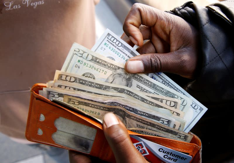 A man displays US dollar notes after withdrawing cash from a bank in Harare