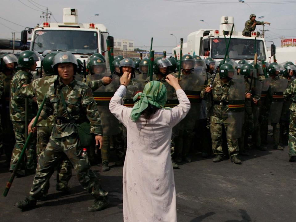 An Uighur woman protests before a group of paramilitary police when journalists visited Xinjiang in July 2009: AP