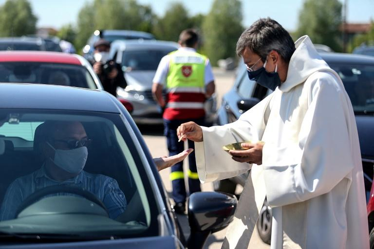 Worshippers who wished to receive communion were asked to switch on their car's hazard lights, and to clean their hands with sanitising gel (AFP Photo/FRANCOIS NASCIMBENI)