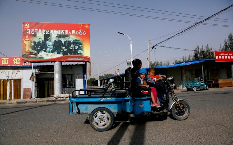 A Uighur woman and children ride past a propaganda poster showing China's President Xi Jinping joining hands with Uighur elders Xinjiang region - AP