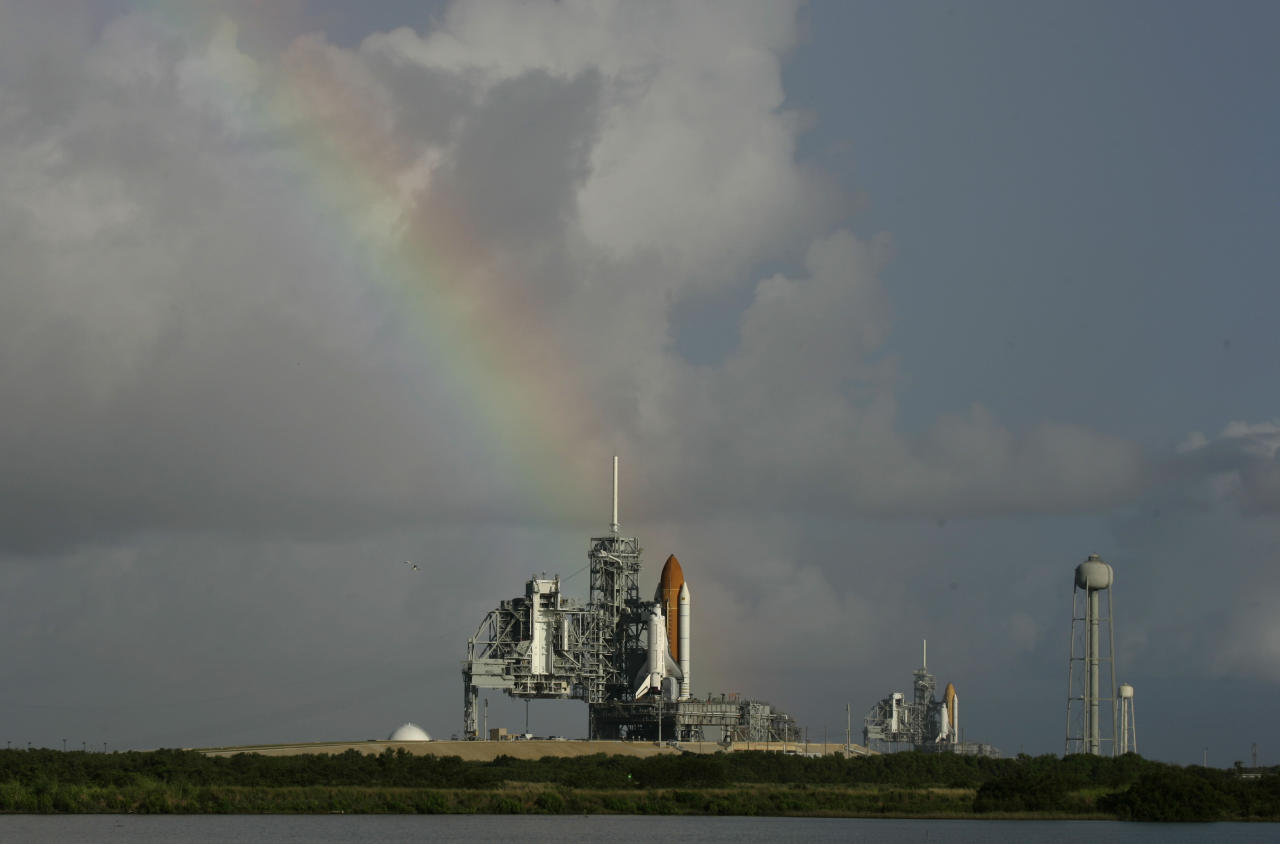 FILE - In this Saturday, Sept. 20, 2008 file photo, space shuttle Atlantis on pad 39A, left, and Endeavour on pad 39B stand ready in front of a rainbow in the early morning at Kennedy Space Center in Cape Canaveral, Fla. Dormant for nearly six years, Launch Complex 39A at NASA's Kennedy Space Center should see its first commercial flight on Feb. 18, 2017. A SpaceX Falcon 9 rocket will use the pad to hoist supplies for the International Space Station. (AP Photo/John Raoux)