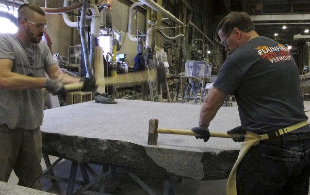 In this Tuesday, Jan. 8, 2019 photo, stone cutters Evan Ladd, left, and Andy Hebert cut a piece of granite at Rock of Ages in Barre, Vt. The granite will be formed into stone monoliths that will be part of a permanent dedication to ground zero rescue and recovery workers expected to be unveiled in late May at the National September 11 Memorial & Museum in New York. (AP Photo/Lisa Rathke)
