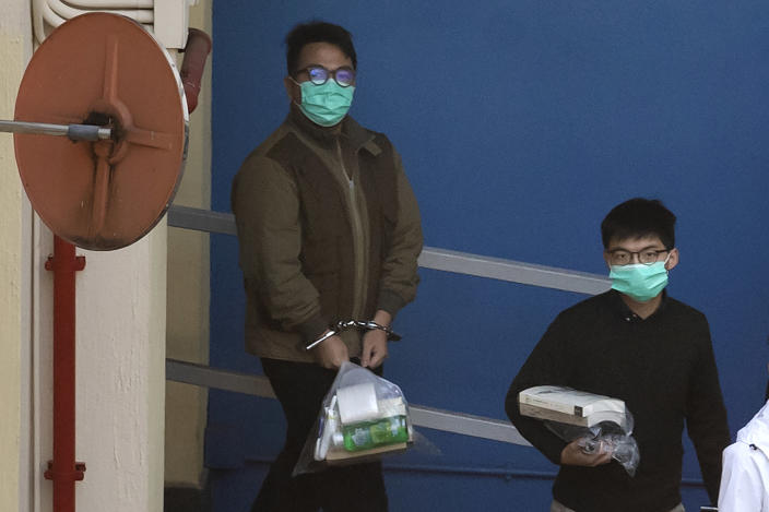 Hong Kong activists Joshua Wong, right, and Ivan Lam, left, are escorted by Correctional Services officers to get on a prison van before appearing in a court, in Hong Kong, Wednesday, Dec. 2, 2020. Prominent Hong Kong pro-democracy activist Wong and two other activists, Lam and Agnes Chow, were taken into custody after they pleaded guilty to charges related to a demonstration outside police headquarters during anti-government protests last year. (AP Photo/Kin Cheung)