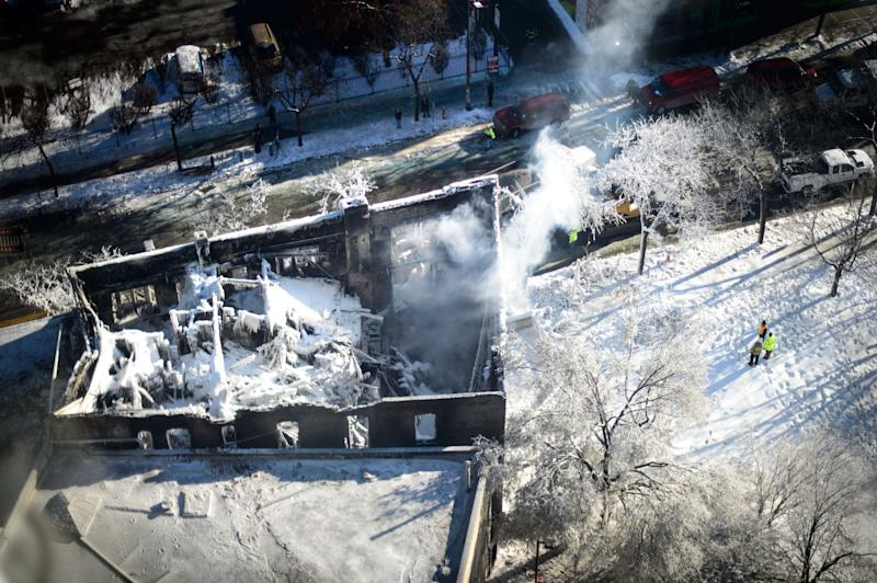 The collapsed rooftop and charred remains is shown on Thursday, Jan. 2, 2014, in Minneapolis, after Wednesday's fire destroyed the building. Fourteen were injured and the cause of the fire is still unclear. (AP Photo/The Star Tribune, Glen Stubbe) MANDATORY CREDIT; ST. PAUL PIONEER PRESS OUT; MAGS OUT; TWIN CITIES TV OUT