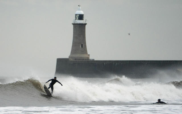 Surfers take on the waves at Tynemouth, north-east England, as the weather is predicted to get much colder over the coming days, Wednesday Jan. 16, 2019. Britain's Met Office has issued a yellow warning for snow and ice over parts of Scotland and northern England, as temperatures are predicted to drop overnight. (Humphreys/PA via AP)