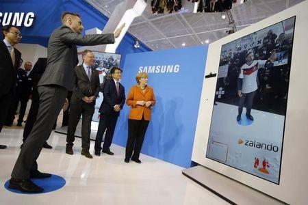 German Chancellor Merkel looks at the mobile online shopping application Zalando at the Samsung booth during the CeBIT technology fair in Hanover