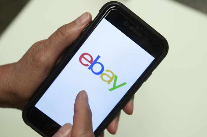 FILE - In this July 11, 2019, file photo, an Ebay app is shown on a mobile phone in Miami. Britain's competition watchdog said Wednesday, Jan. 8, 2020 that Facebook and eBay pledged to crack down on the trade in fake reviews at its request, removing hundreds of accounts, pages and groups involved in the illicit business. (AP Photo/Wilfredo Lee, File)