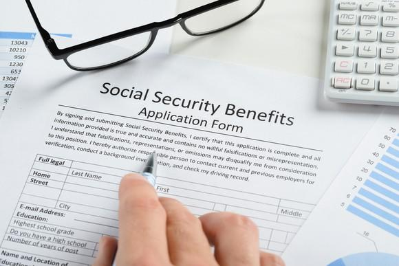 A person filling out a Social Security benefits application form with a pen. Black eyeglasses and calculator sit nearby.