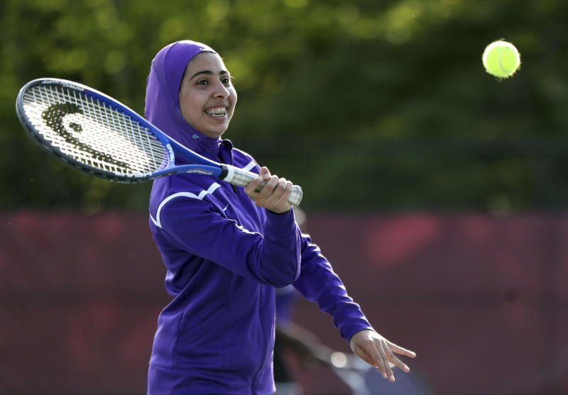 In this May 24, 2017, photo Tabarek Kadhim, a sophomore at Deering High School in Portland, Maine, wears a sports hijab while playing a tennis match in Windham, Maine. Deering High School is providing sport hijabs with the goal of making Muslim girls comfortable and boosting their participation in sports. Tennis co-captains Liva Pierce and Anaise Manikunda solicited private donations to avoid criticism for using taxpayer funds on religious apparel, and ended up with enough to outfit all teams, including lacrosse, soccer, volleyball, softball, field hockey and track. (AP Photo/Robert F. Bukaty)