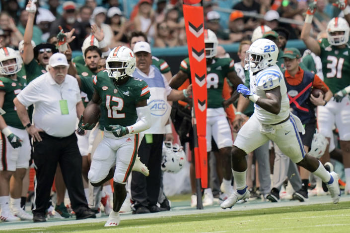 Miami wide receiver Brashard Smith (12) runs to score a touchdown past Central Connecticut State safety Zibassie Edwards (23) during the first half of an NCAA college football game, Saturday, Sept. 25, 2021, in Miami Gardens, Fla. (AP Photo/Lynne Sladky)
