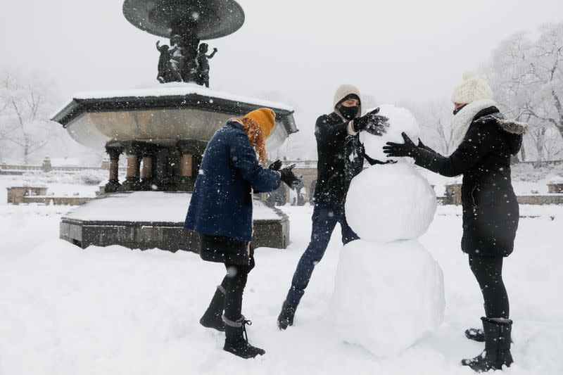 People build a snowman in the Bethesda Fountain in Central Park, in New York City