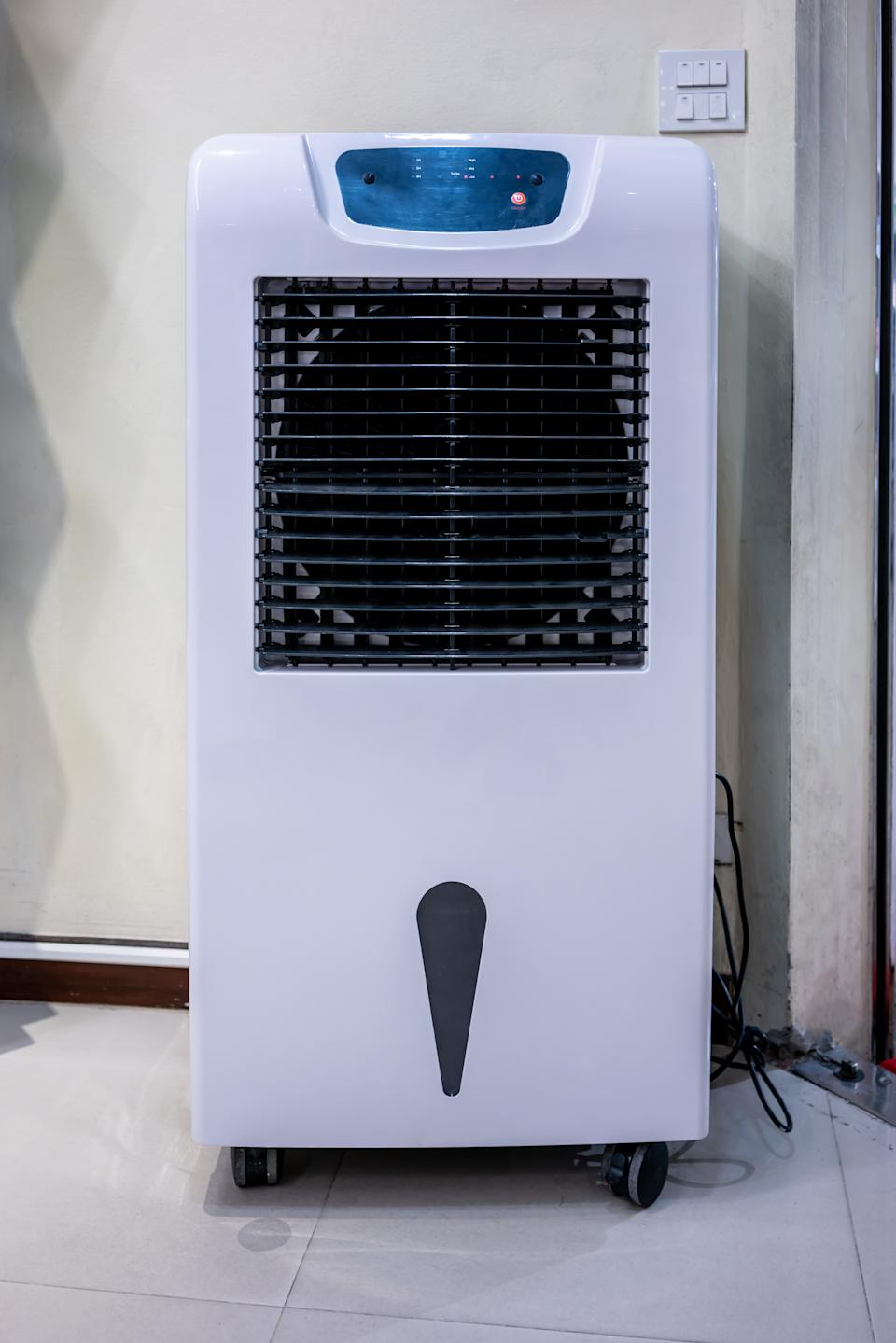 Electronic room tower fan and humidifier on white wall background