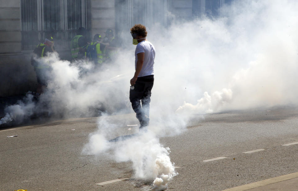 A man wears a mask amidst tear gas canisters during a yellow vest demonstration in Paris, Saturday, April 20, 2019. French yellow vest protesters are marching anew to remind the government that rebuilding the fire-ravaged Notre Dame Cathedral isn't the only problem the nation needs to solve. (AP Photo/Michel Euler)
