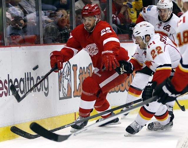 Detroit Red Wings' Brian Lashoff (23) and Calgary Flames' Lee Stempniak (22) chase the loose puck during the first period of an NHL hockey game, Thursday, Dec. 19, 2013, in Detroit. (AP Photo/Duane Burleson)