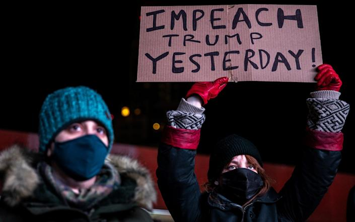 Protesters holding up a sign saying Impeach Trump Yesterday - Jeenah Moon/Reuters