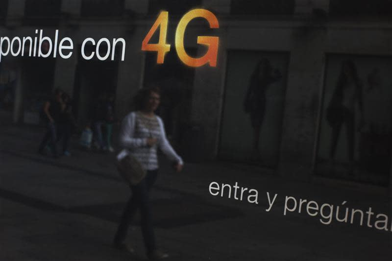 A woman is reflected in an advertisement for 4G services in a shop window in central Madrid
