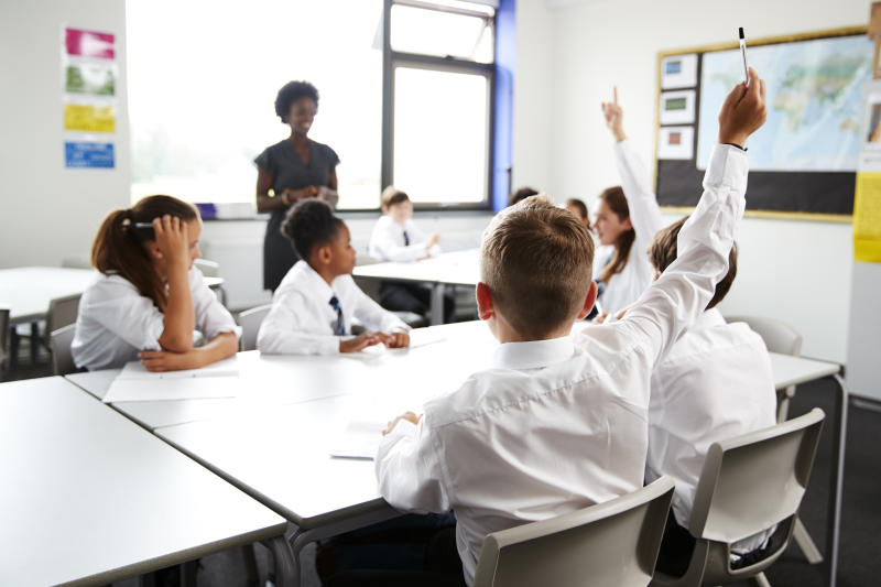 High School Students Wearing Uniform Raising Hands To Answer Question Set By Teacher In Classroom