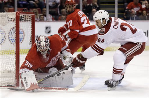 Detroit Red Wings goalie Jimmy Howard, left, stops a shot by Phoenix Coyotes center Kyle Chipchura (24) in the first period of an NHL hockey game in Detroit, Monday, April 22, 2013. (AP Photo/Paul Sancya)