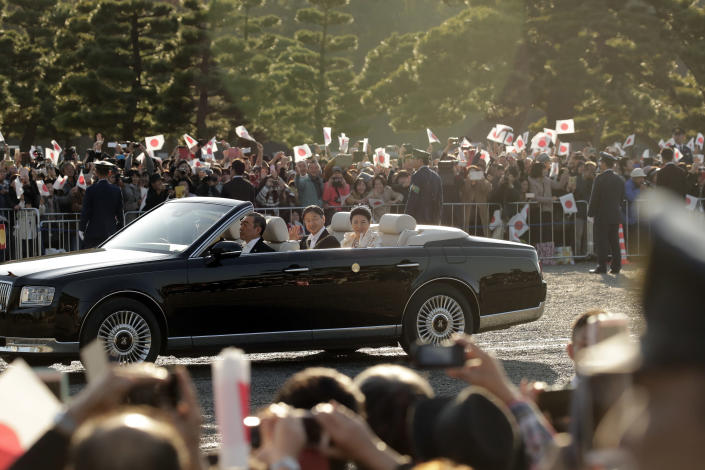 Japanese Emperor Naruhito and Empress Masako wave to spectators during the royal motorcade in Tokyo, Sunday, Nov. 10, 2019. (AP Photo/Jae C. Hong)
