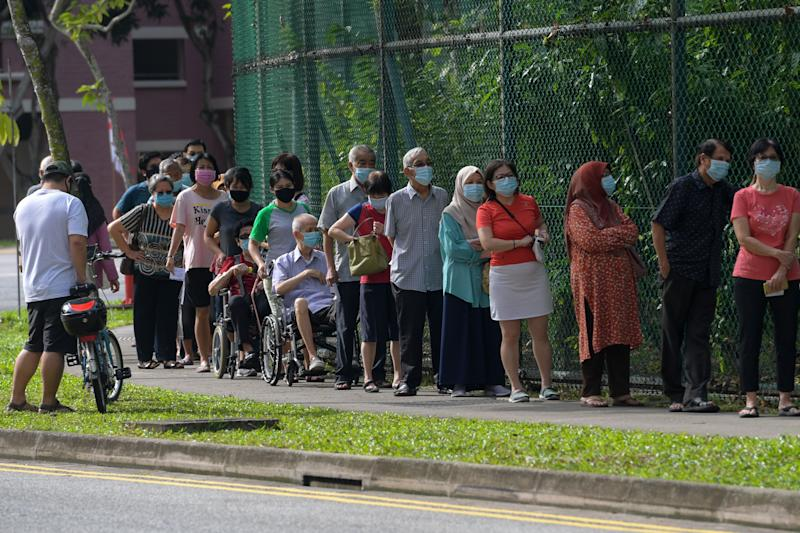 Voters wearing face masks wait to enter a school, temporarily used as a polling station, to cast their ballots during the general election in Singapore on July 10, 2020. - Wearing masks and gloves and being careful to observe social distancing, Singaporeans voted in a general election on July 10 as the city-state struggles to recover from a coronavirus outbreak. (Photo by Roslan RAHMAN / AFP) (Photo by ROSLAN RAHMAN/AFP via Getty Images)