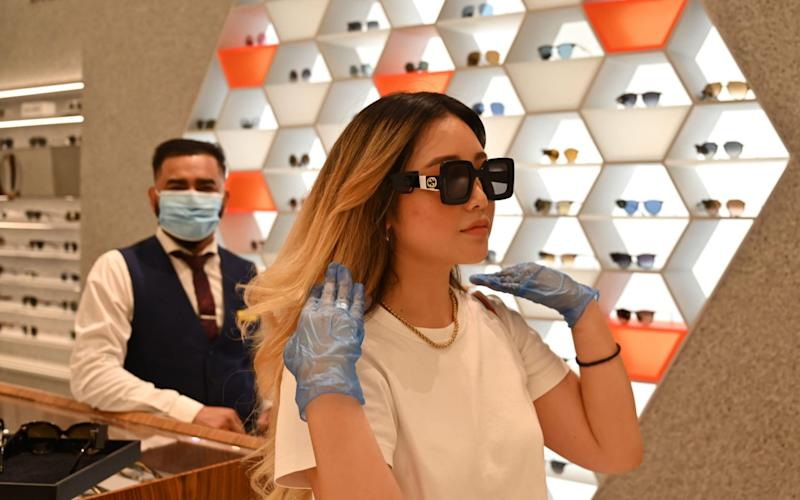 A customer wearing protective gloves tries on sunglasses as a member of staff looks inside Selfridges department store on Oxford Street in London - GLYN KIRK/AFP