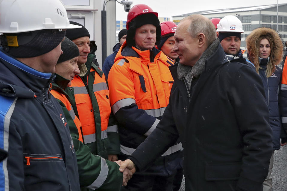 """Russian President Vladimir Putin, right, greets workers as he attends an opening ceremony of the road junction of the M-10 """"Russia"""" highway, connecting Moscow and St. Petersburg, in Khimki outside Moscow, Russia, Tuesday, Jan. 26, 2021. (Mikhail Klimentyev, Sputnik, Kremlin Pool Photo via AP)"""