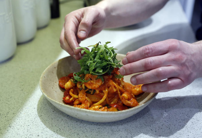 "Jon Watts, demonstrates his cooking skills for the Associated Press by making a prawn linguini at a friends kitchen in Codicote, Welwyn, England, Thursday, April 15, 2021. Jon Watts was 18 years old when he woke up in a prison cell and decided he had to change. He enrolled in every course he could find, from mathematics to business. But he says it was a program founded by Prince Philip, the Duke of Edinburgh, that gave him a ""passion for food"" and a career as a chef when he got out of prison 3 1/2 years later. (AP Photo/Alastair Grant)"