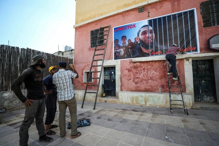 Men affix a banner calling for the release of Tauqir Sharif to a building  in the town of Atme in Syria's rebel-held northwestern Idlib province