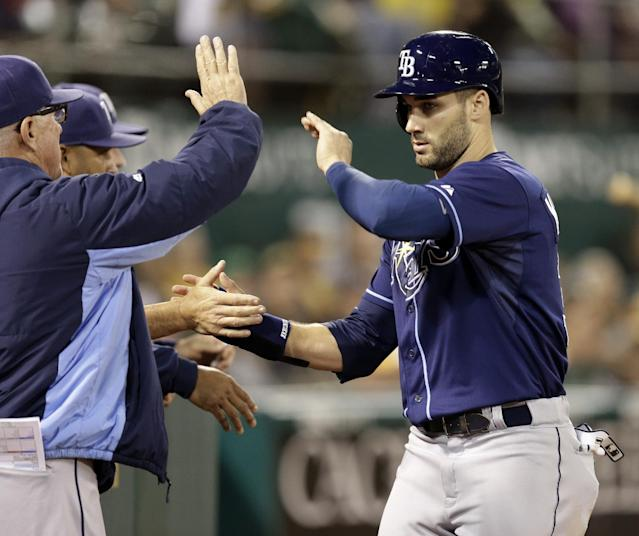 Tampa Bay Rays' Kevin Kiermaier, right, is congratulated after scoring against the Oakland Athletics in the fifth inning of a baseball game Monday, Aug. 4, 2014, in Oakland, Calif. (AP Photo/Ben Margot)