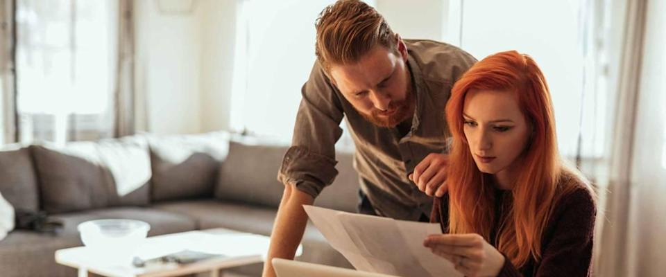 Young couple calculating bills at home.