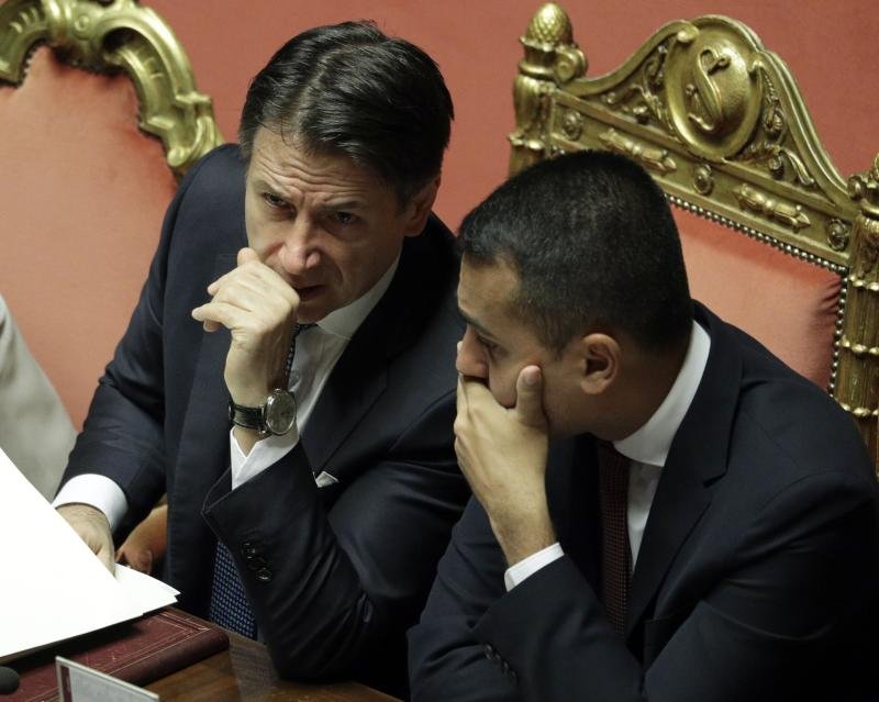 Italian Premier Giuseppe Conte, left, shares a word with Foreign Minister Luigi Di Maio at the Senate ahead of a second confidence vote on his coalition government, in Rome, Tuesday, Sept. 10, 2019. Conte on Monday won the first of two mandatory confidence votes on his four-day-old coalition of rival parties, after a day of fielding insults during a boisterous Parliament session from an opposition outraged that Italy got a new government instead of a new election. (AP Photo/Andrew Medichini)