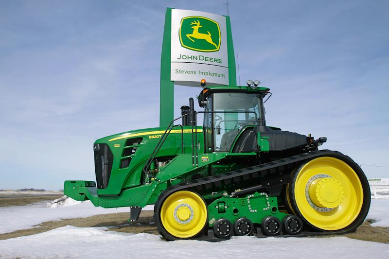 FILE- In this Feb. 13, 2011, file photo, a John Deere tractor is parked at the Stevens Implement Company, a John Deere dealership, in Petersburg, Ill. Deere & Co. said Wednesday, Nov. 21, 2012, that it earned $687.6 million for the quarter, or $1.75 per share. (AP Photo/Seth Perlman, File)