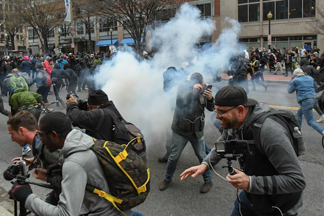 Protesters and journalists scramble as stun grenades are deployed by police during the demonstrations on Jan. 20. (Bryan Woolston/Reuters)