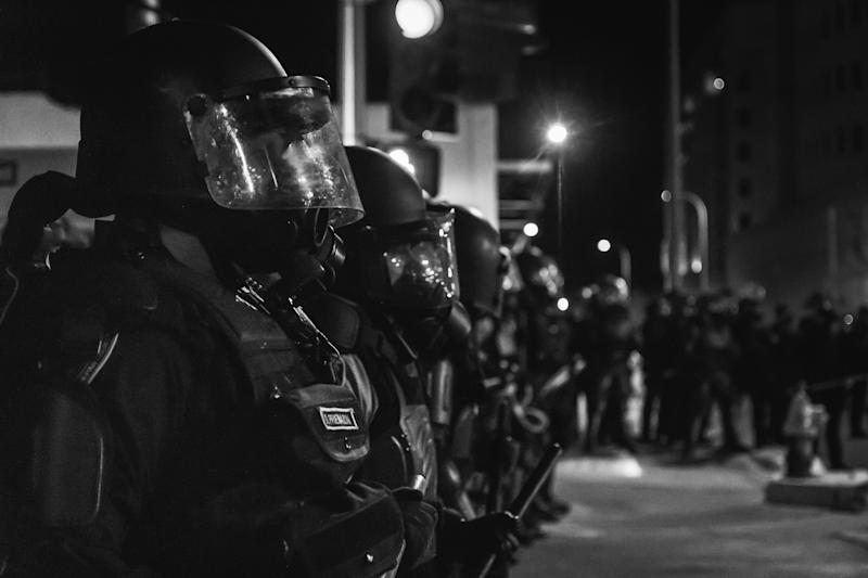 Albuquerque police officers observe a protest in March 2014, just weeks before the U.S. Department of Justice released a scathing report about the department's unconstitutional practices.
