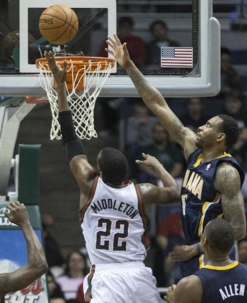 Milwaukee Bucks' Khris Middleton (22) shoots the ball over Indiana Pacers' Rasual Butler during the second half of an NBA basketball game on Wednesday, April 9, 2014, in Milwaukee. (AP Photo/Tom Lynn)