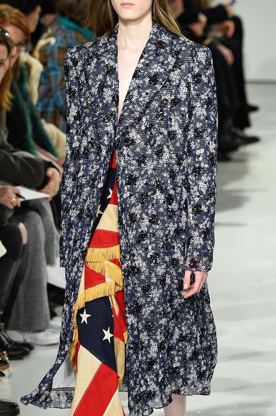 """<p>At Raf Simons's debut collection for Calvin Klein, patriotic red, white, and blue ensembles were cast against David Bowie's """"This Is Not America"""" song. In this look, Simons styles an American flag beneath a coat. (Photo: Getty Images) </p>"""