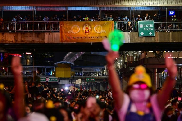 A sign that reads 'The Rubber Duck Revolution' is displayed from an overhead bridge as pro-democracy protesters take part in an anti-government rally at Lat Phrao intersection