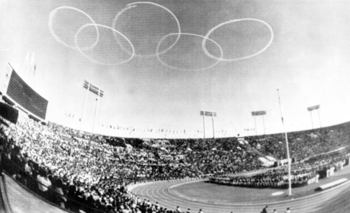 FILE - In this Oct. 10, 1964, file photo, vapor trails from Japanese Self-Defense Force jets from the Olympic emblem of five rings above the National Stadium in Tokyo for the official opening of the XVIII Olympiad, first even held in Asia. The famous 1964 Tokyo Olympics highlighted Japan's resiliency. It was a prospering country that was showing off bullet trains, transistor radios, and a restored reputation just 19 years after devastating defeat in World War II. Now Japan and Tokyo are on display again, attempting to stage the postponed 2020 Tokyo Olympics in the midst of a once-in-a century pandemic. (AP Photo, File)