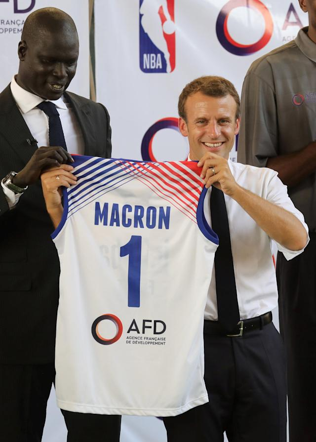 French President Emmanuel Macron recieves a jersey from managing director of NBA Africa, Amadou Gallo Fall, at the French Louis Pasteur high school school in Lagos, Nigeria, July 4, 2018. Ludovic Marin/Pool via Reuters