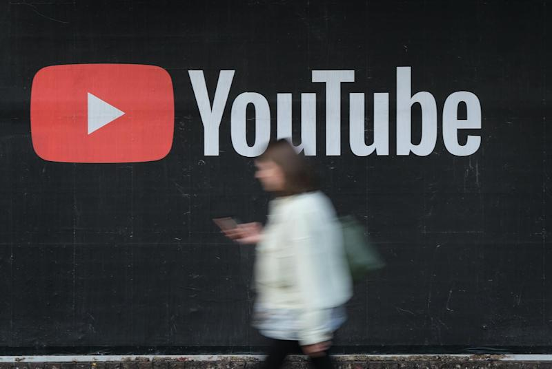 A young woman with a smartphone walks past a billboard advertisement for YouTube on September 27, 2019 in Berlin, Germany: Sean Gallup/Getty Images