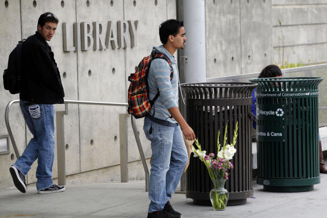 Santa Monica College students returning to class walk by flowers left near the library on the campus in Santa Monica, Calif., Monday June 10, 2013. Santa Monica College reopened under extra security Monday except for the library, where police shot and killed a heavily armed gunman after a rampage that left five people dead on Friday. Students who fled Friday would be able to resume final examinations and retrieve backpacks, cars and other belongings, according to the college website. (AP Photo/Nick Ut)