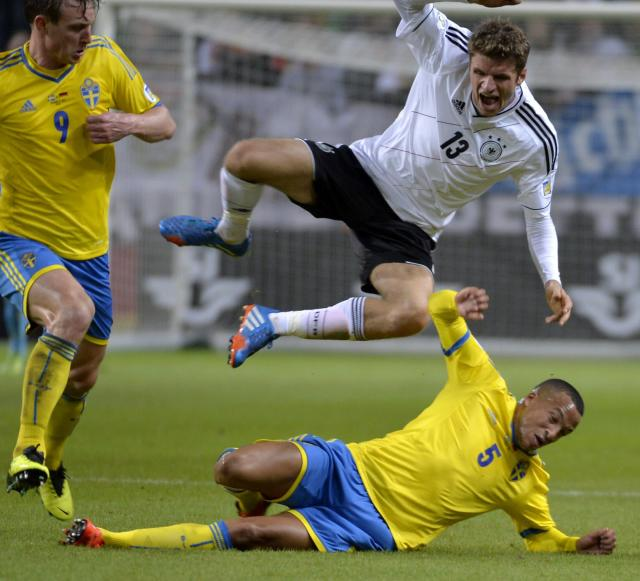 Germany's Thomas Muller, top, jumps over Sweden's Martin Olsson as Sweden's Kim Kallstrom, left, looks on during the 2014 World Cup group C qualifying soccer match between Sweden and Germany at Friends Arena in Stockholm, Sweden, on Tuesday Oct. 15, 2013. (AP Photo/TT, Anders Wiklund)