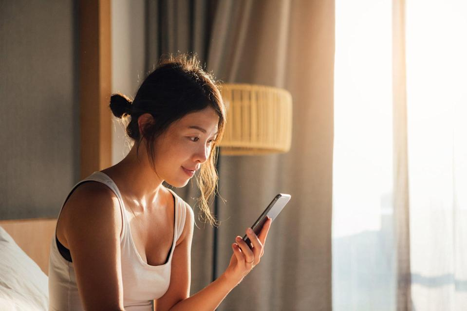 Portrait of young Asian woman holding smartphone while waking up in bed in the morning.
